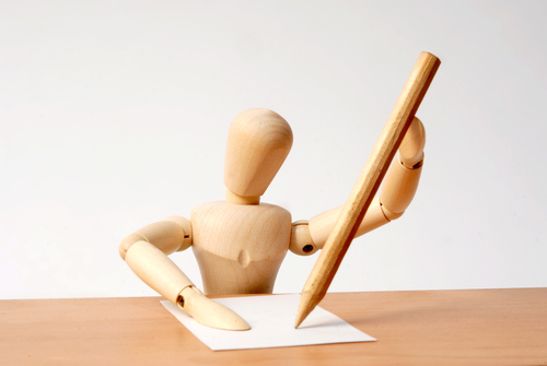 Small wooden man writing at desk