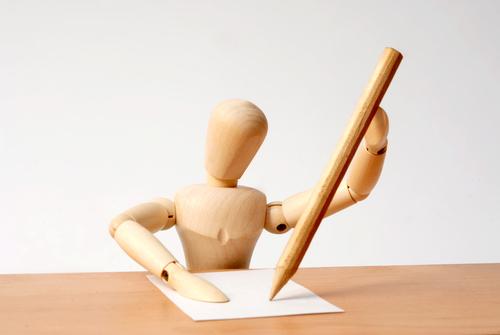 Small wooden man writing at desk