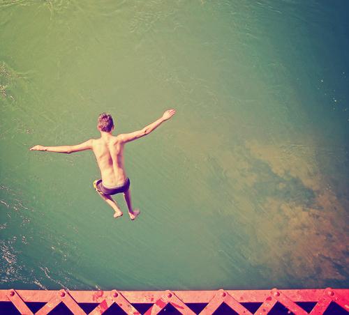 Boy jumping off bridge into water