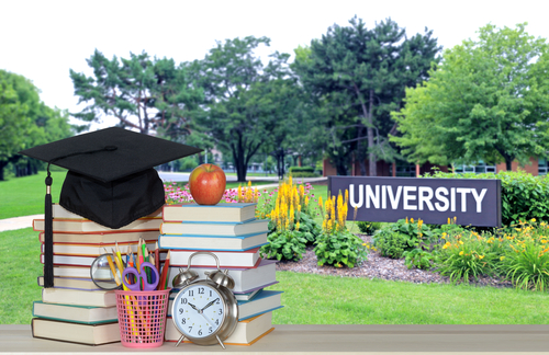 Grad Hat on books infront of a university sign